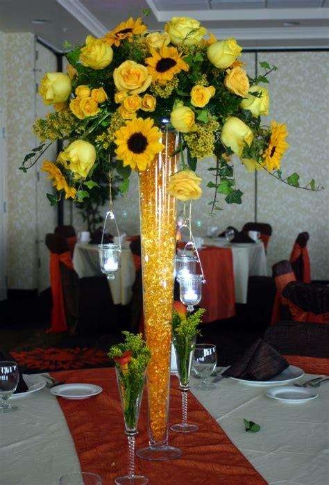 monochromatic centerpiece features sunflowers roses