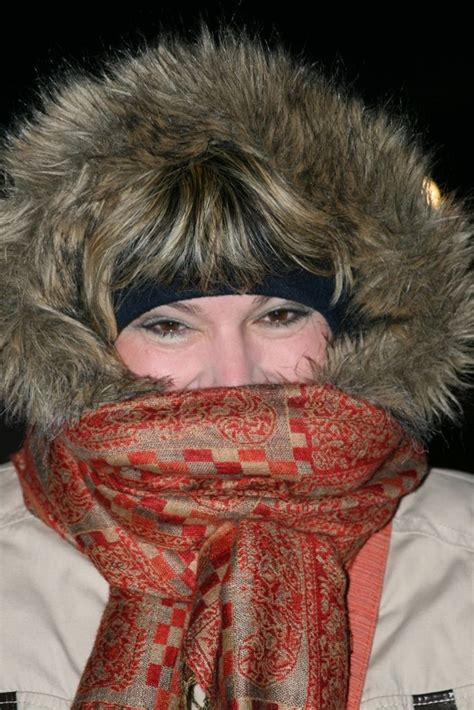 Bundled up woman hood up and face covered by scarf in 2020