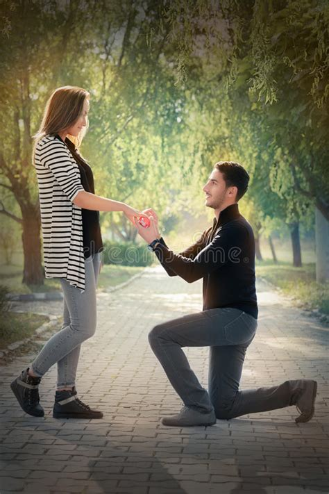 kneeling man proposing   engagement ring stock photo