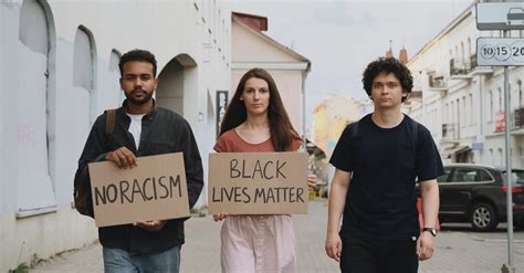 People On The Street Holding Placards With No Racism And