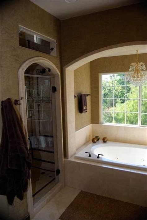 arched shower door tiled  travertine  tub accented