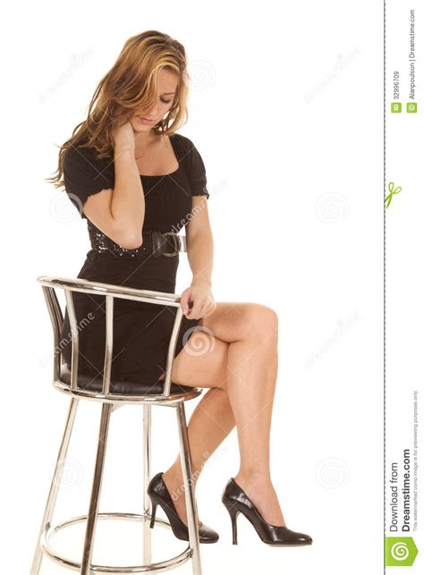 in black dress sitting on chair stock image image