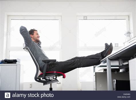 sitting on office chair with up on desk stock
