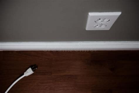 Unplugged Cord On Floor Beside Electrical Outlet Stock
