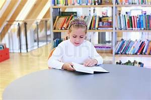 School girl reading a book in library | Stock Photo ...