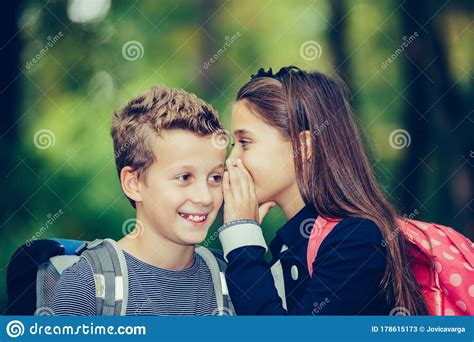 student whispering   students ear stock image