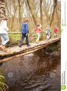 Group Of Children Crossing Stream On Wooden Bridge Stock ...