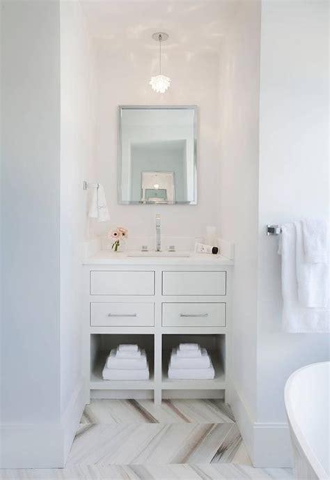 small white bathroom  gray marble herringbone floor