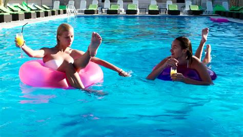 Girl Swimming In A Pool On Inflatable Circles, Floating