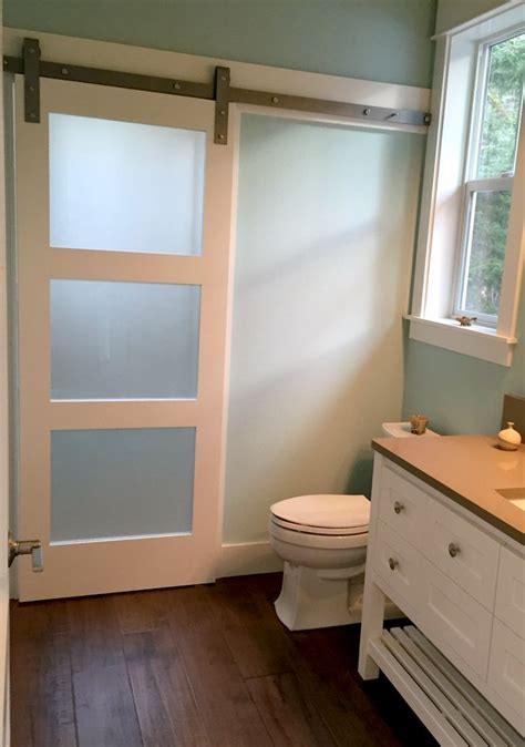 frosted glass barn door adds privacy  shower room