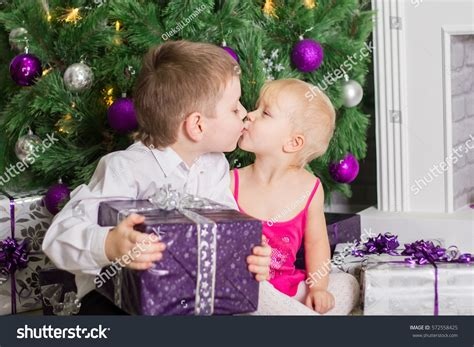 Children Exchange Gifts Kiss Under Festive Stock Photo
