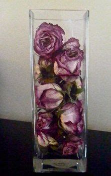 dried roses displayed   glass vase  simple