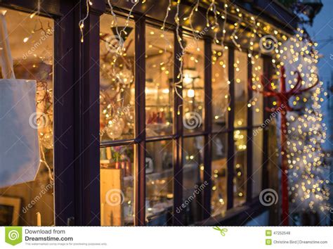 hanging christmas lights on windows outside festive lights outside a shop window stock photo image