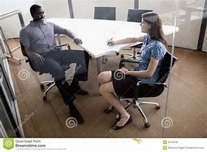 Two Business People Sitting At A Conference Table And ...