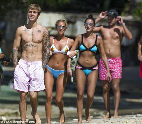 Justin Bieber attracts bikini-clad fans while hitting the beach on his Caribbean vacation ...