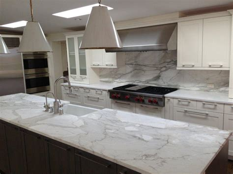 a remodeled kitchen with a slab of granite island matching