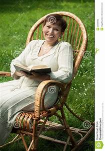 Happy Mature Woman With Book In Rocking Chair Royalty Free