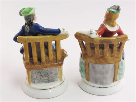 colonial figurines sitting in chairs made in occupied
