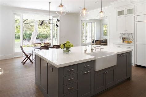 kitchen island with farmhouse sink light gray center island with brass barstools 8248