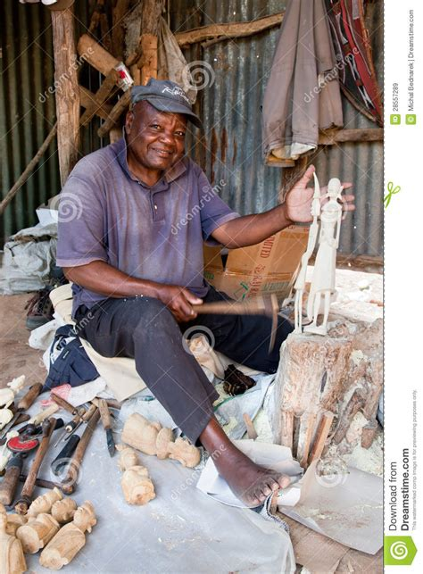 kenya africa december   man carving figures  wood