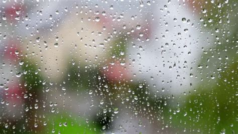 heavy rain falling  large window pane raindrops