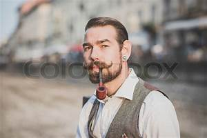 Handsome big moustache hipster man smoking pipe in the ...