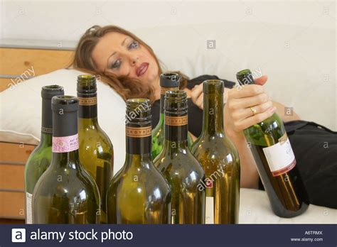 Young Woman Lying On Couch Holding Bottle Of Wine After
