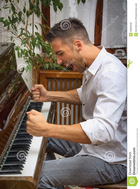 young man playing classical piano shouting stock photo