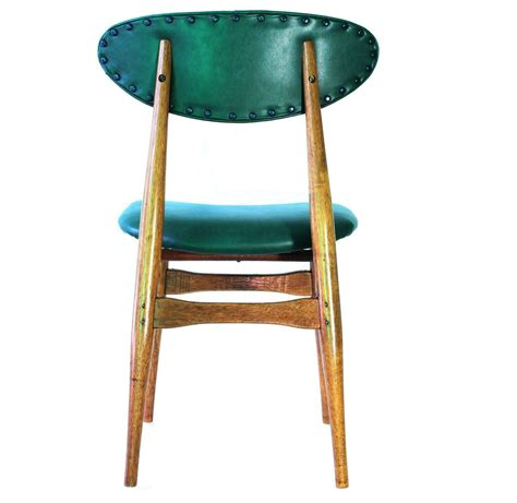 set of four teak dining chairs with green vinyl