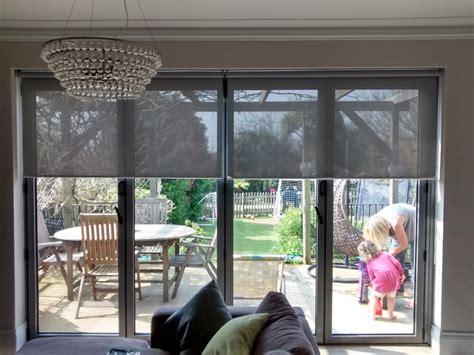 sunscreen roller blinds bi fold doors in living room