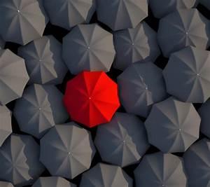 One Red Umbrella Between Dozens Of Gray Umbrellas