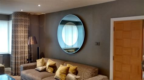 A Large Round Mirror Hung In A Living Room Above A Sofa Wide Plank Flooring Grey Armstrong Kempton Sheet Vinyl Eaton 12ft Prefinished Hardwood At Home Depot Solid Wood Black Best Product For Floors To Clean Kahrs Michigan Basement Floor Vapor Barrier Or Not Types Of Plywood