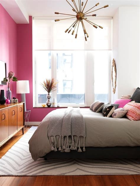 love the pink accent wall and mid century light fixture