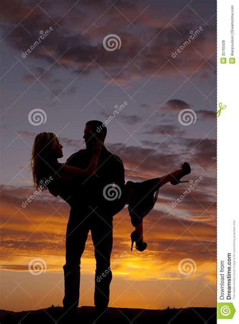 silhouette man lifting woman     stock