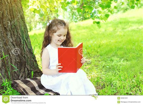 happy child reading book  grass  summer stock photo