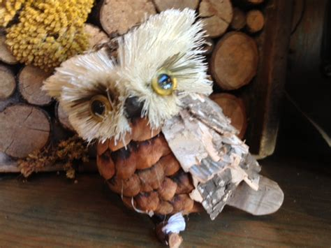 owl creations from pine cones and fluff reflections on a blue eyed owl light words