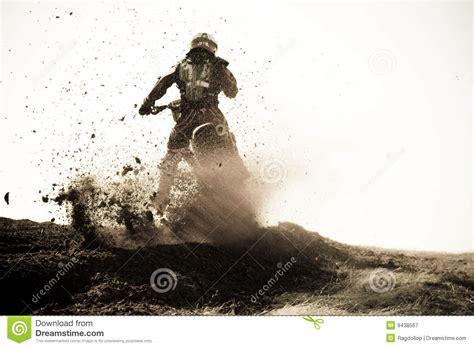 Motocross Racer Roosts Dirt Berm On Track. Stock Image
