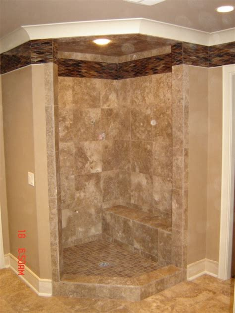 this shower has a travertine field tile with a glass