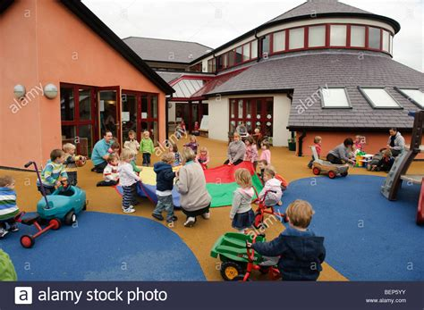 small children outdoors at a pre school nursery 121   small children playing outdoors at a pre school nursery creche or BEP5YY