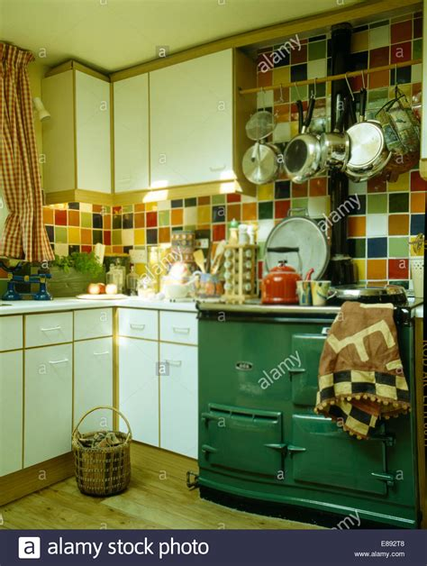 green aga oven in kitchen with multi coloured wall tiles