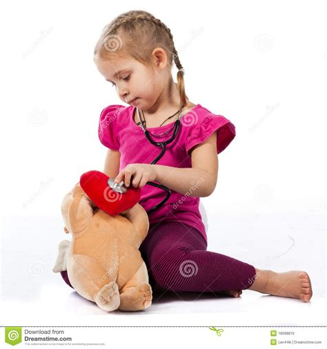 Beautiful Girl Playing Doctor With A Doll Stock Photo
