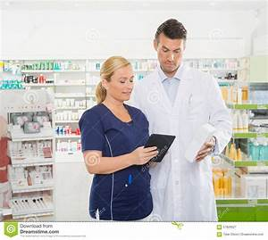 Assistant Using Digital Tablet While Pharmacist
