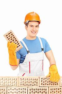 Smiling Male Builder Building A Brick Wall Stock Image