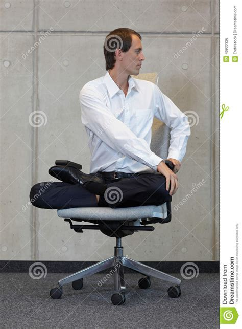 businessman in lotus pose on office chair practicing