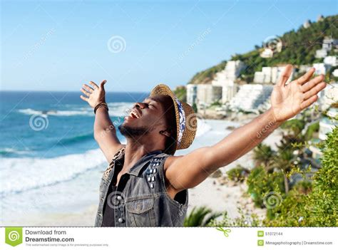 Cheerful Young Man With Arms Spread Open At The Beach