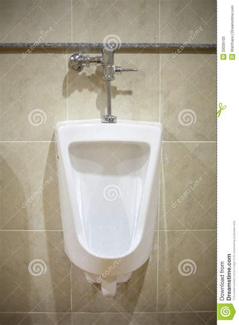 wall mounted white ceramic toilet  brown tiled bathroom