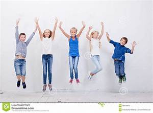 Group of happy young people jumping on white