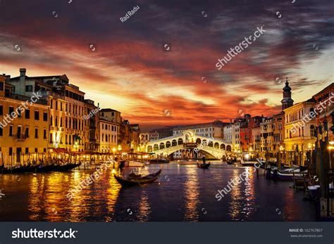 Ponte Rialto And Gondola At Sunset In Venice Italy Stock