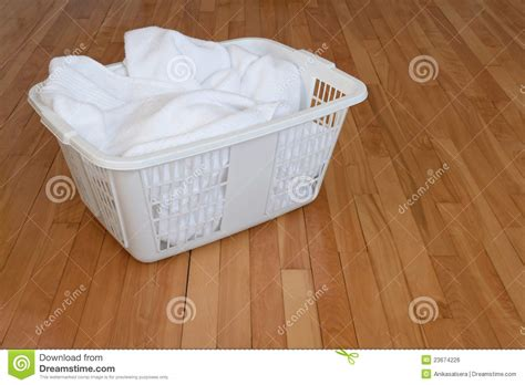 Laundry Basket With White Towels On Wooden Floor Stock