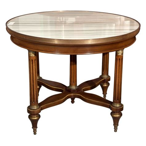 The circular top with glass insert, atop a narrow fluted frieze with patera carvings, raised on four squared tapering legs. French Marble Top Mahogany Coffee Table by Jansen France $3650 1940s French Empire style ...